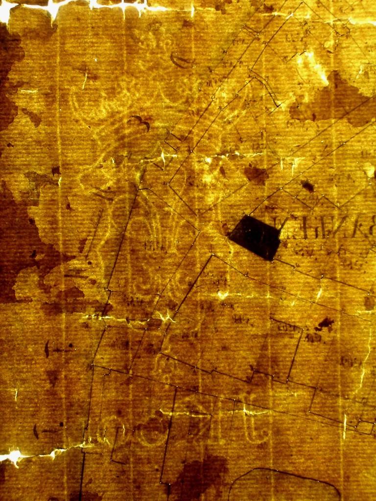 """Vannmerker i kartet fra 1794. Her ses ett vannmerke med en lilje under en krone med de speilvendte innitalene """"JK 100"""". Kjede- og bunntrådene i papiret er tydelige. Fotograf: Kristin Ramsholt."""