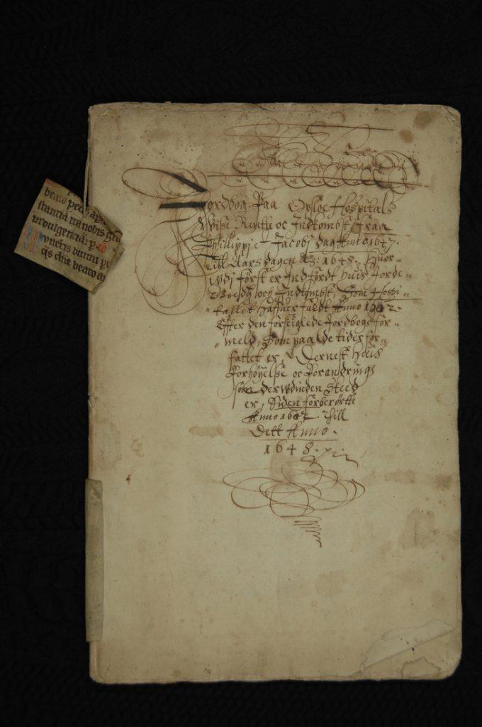 Forsiden til jordeboka fra 1648, med oversikt over Oslo Hospitals eiendommer. En del av et middelaldermanuskript ble brukt både til å forsterke ryggen, en annen del er festet til innbindingen. Foto: Kirsti Gulowsen, Oslo byarkiv.