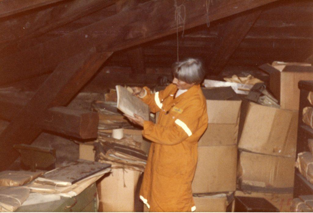 Kommunearkivar Marcia Berg studerer etterlatt arkivmateriale på et loft i Storgata i juni 1985. Foto: Oslo byarkiv.
